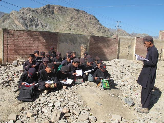 Komeke zarokên xwendekar ên li bakurêrojavayê Pakîstanê li derve perwerde dibin. Dibistana wan di şerê Talebanê ya li dijî Pakîstanê de hatiye hilweşandin.